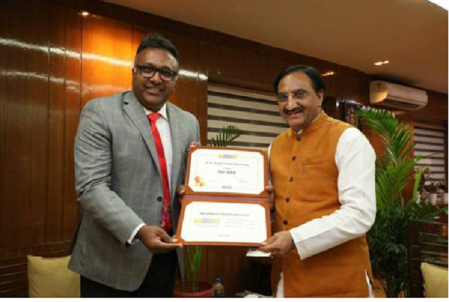 PIB: Vice Chancellor Prof. C. Raj Kumar presenting the QS Certificate of Achievement (for Entry into QS World University Rankings 2020) to the Union Minister of Human Resource Development, Dr. Ramesh Pokhriyal 'Nishank'