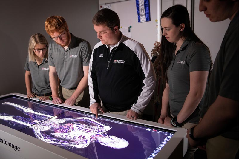 Photo Courtesy: University of Nebraska Omaha-UNO Athletic Training Instructor Sam Wilkins walks students through using an Anatomage Table, which provides a virtual, interactive experience in understanding the inner workings of the human body